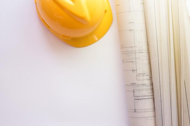 Casque de sécurité et blueprint sur fond blanc. vue de dessus avec copie sapce.