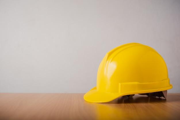 Casque de sécurité casque jaune sur fond de bois