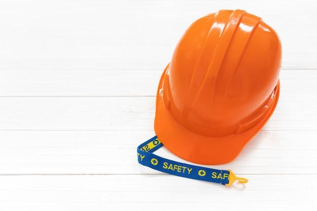 Casque de sécurité ingénieur ou contremaître sur un fond en bois blanc.