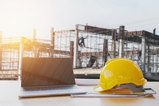 Casque de sécurité et ordinateur portable sur la table dans le site de la construction