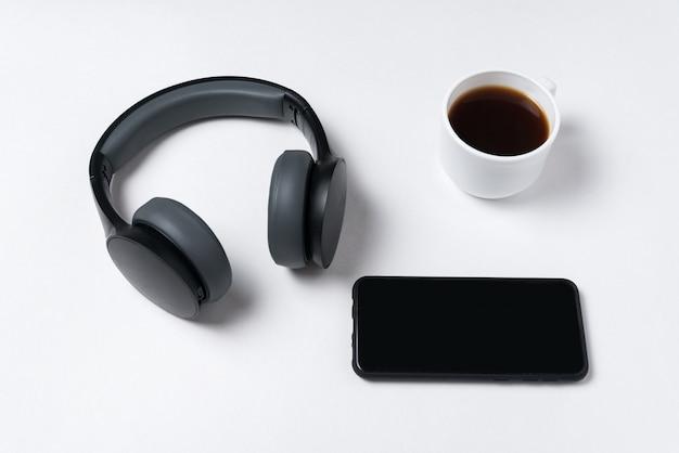 Casque, smartphone et tasse de café sur blanc espace copie