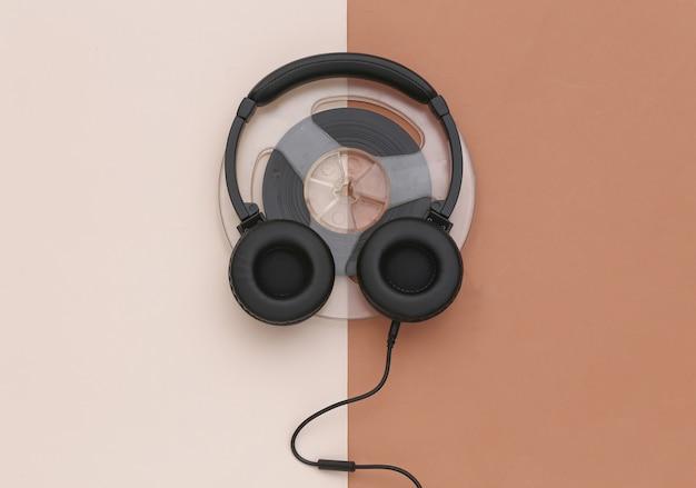 Casque stéréo et bobine audio magnétique sur fond beige marron. vue de dessus