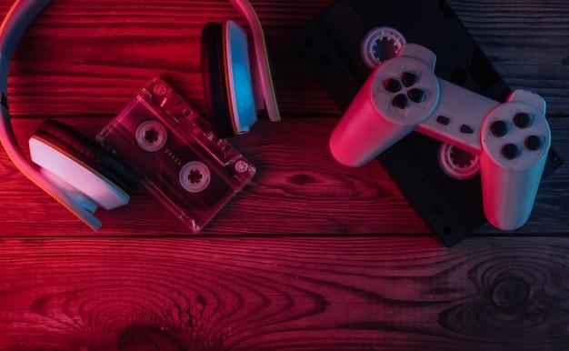 Casque stéréo, cassette audio et vidéo, manette de jeu sur une surface en bois. lumière néon rouge et bleue