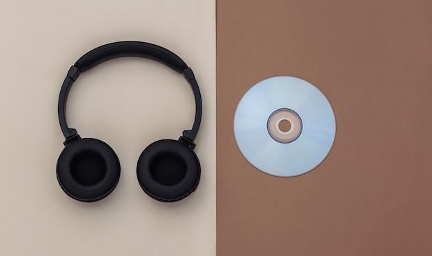 Casque stéréo avec disque cd sur fond beige marron. vue de dessus