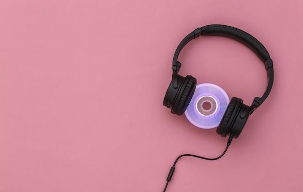 Casque stéréo avec disque cd sur fond rose. vue de dessus