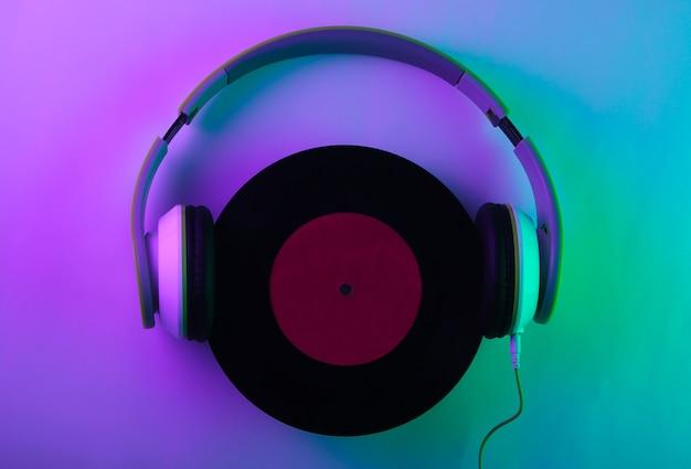 Casque stéréo avec un disque vinyle. néon, lumière holographique