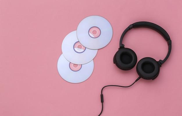 Casque stéréo avec disques cd sur fond rose. vue de dessus