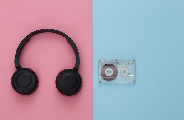 Casque stéréo noir avec cassette audio rétro sur pastel bleu rose