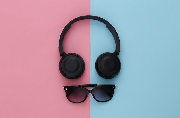 Casque stéréo noir et lunettes de soleil sur fond rose-bleu