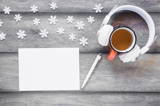 Casque et thé près des flocons de neige et de la feuille de papier