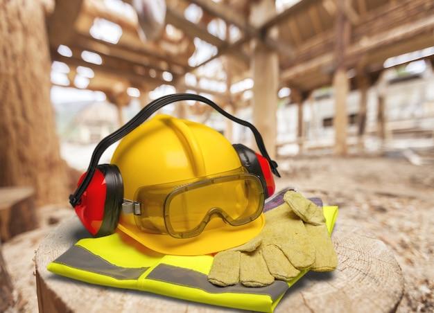 Casque de travail jaune, gants et lunettes de travail sur fond de bois