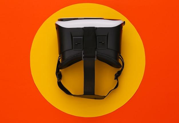 Casque vr sur orange avec cercle jaune. gadgets modernes. réalité virtuelle