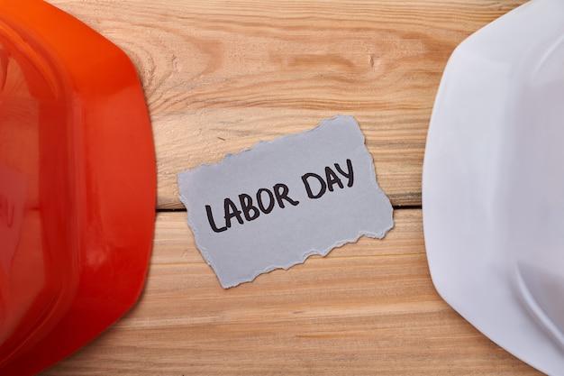 Casques et carte de la fête du travail. casques durs sur fond de bois. la sécurité est toujours une priorité.