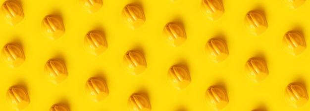 Casques durs sur fond jaune à la mode, image panoramique