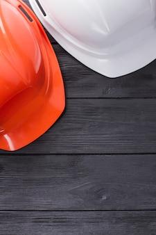 Casques de travailleurs de la construction sur bois foncé. vue de dessus à plat.