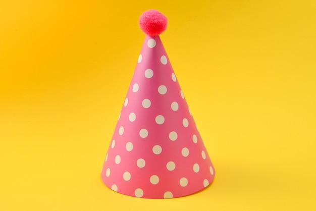 Casquette d'anniversaire rose sur fond jaune. copiez l'espace.