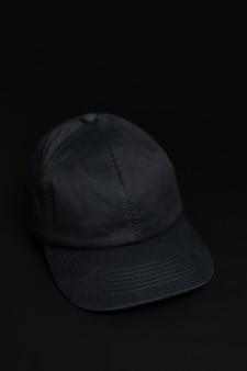Casquette / chapeau en tissu noir sur fond noir foncé.