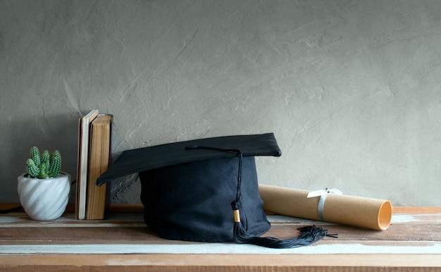 Casquette d'obtention du diplôme, chapeau avec papier degré sur table en bois.