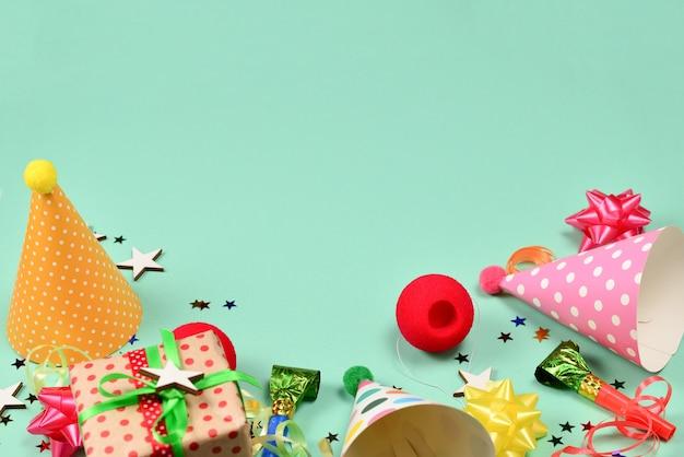 Casquettes d'anniversaire, cadeau, confettis, rubans, étoiles, nez de clown sur fond vert. espace pour le texte ou la conception.