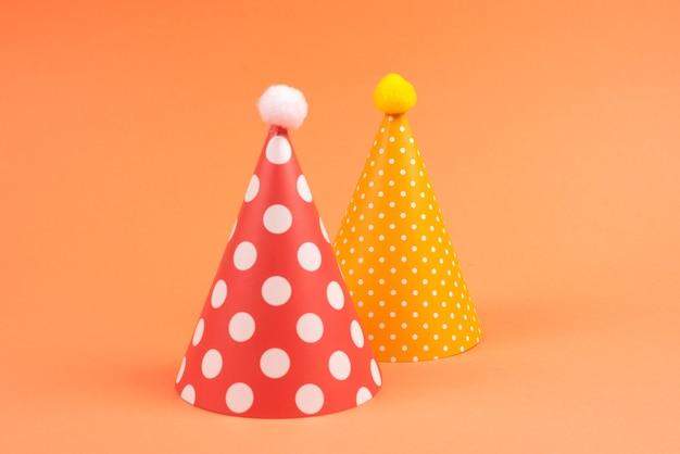 Casquettes d'anniversaire colorées sur fond orange. vue de dessus.
