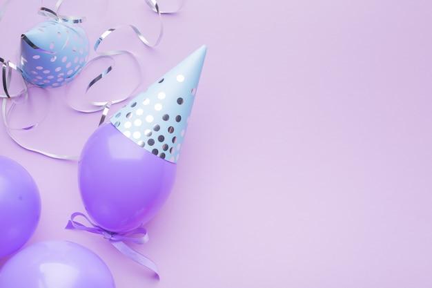 Casquettes bleues, boules violettes et serpentine argentée sur fond de papier violet. fond de vacances.