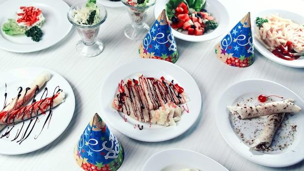 Casquettes festives et plats variés sur la table du restaurant pour enfants. vacances pour les enfants