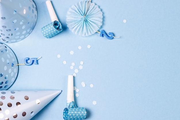 Casquettes de papier d'anniversaire avec des confettis de bougies et des pailles sur bleu
