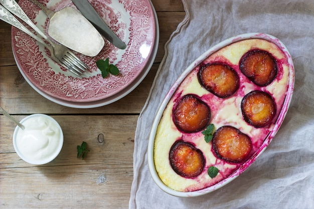 Casserole de caillé tendre aux prunes et à la semoule, servie avec des feuilles de cannelle et de menthe