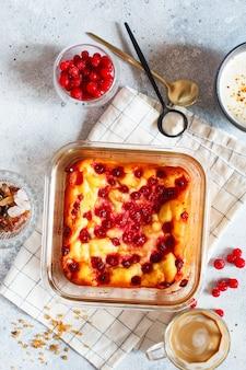 Casserole de fromage cottage cuit au four avec des groseilles rouges.