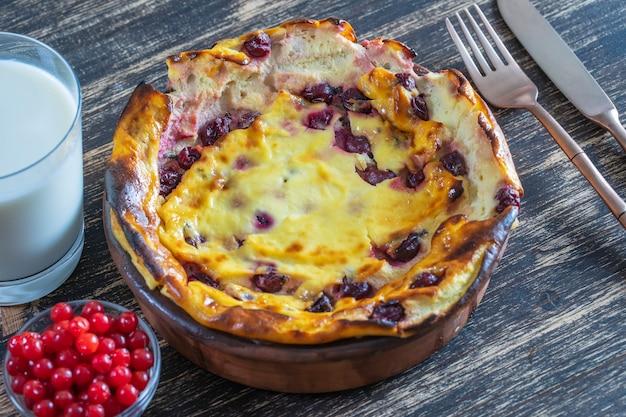 Casserole de fromage cottage sucré avec groseille et semoule sur table en bois. bol en céramique avec casserole de fromage cottage cuit au four, close up