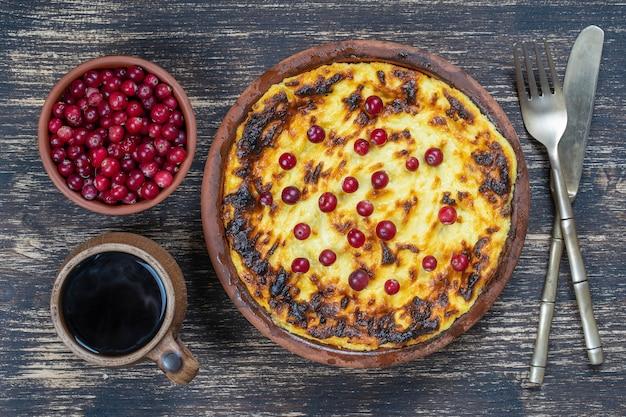 Casserole de fromage cottage sucré avec raisins secs et semoule sur table en bois. bol en céramique avec casserole de fromage cottage cuit au four, gros plan, vue de dessus
