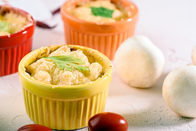 Casserole de fromage gros plan aux champignons dans des noix de coco colorées sur fond blanc