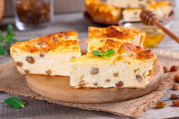 Casserole de fromage avec des raisins secs sur plaque sur table en bois, gros plan