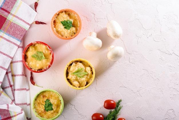 Casserole de fromage vue de dessus aux champignons dans les noix de coco colorées sur fond rose clair avec torchon de cuisine