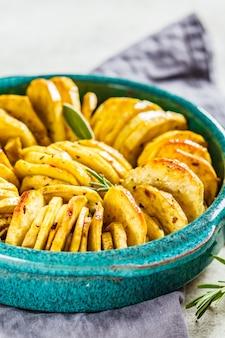 Casserole de patates douces blanche cuite au four avec des herbes dans un plat bleu.