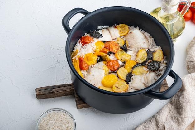 Une casserole de poisson fabuleux, avec du riz basmati et des tomates cerises, sur fond blanc avec copie espace pour le texte
