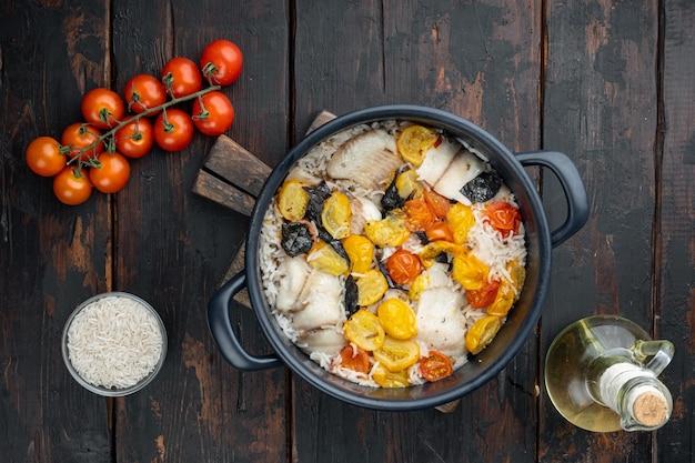 Une casserole de poisson fabuleux, avec du riz basmati et des tomates cerises, sur une vieille table en bois, vue de dessus