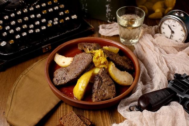 Une casserole en pot avec des morceaux d'agneau cuits à l'oignon et au coing