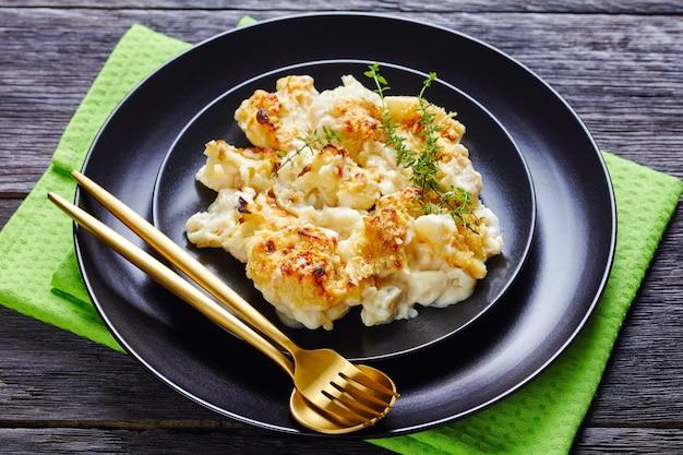 Casserole saine de fromage chou-fleur servi sur une plaque noire avec du thym frais sur le dessus sur une table en bois avec une serviette verte et des couverts dorés, close-up