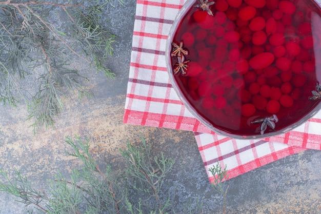 Une casserole sombre de jus rouge sur marbre