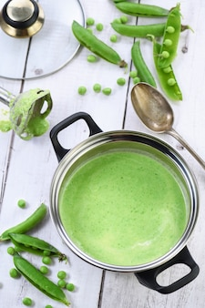 Casserole de soupe fraîchement préparée de purée de pois verts et de crème sur la table.