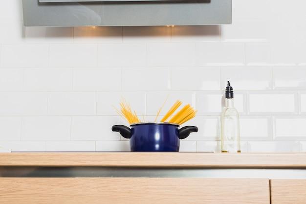 Casserole sur la table de cuisson dans la cuisine avec une bouteille d'huile