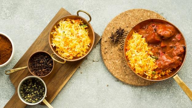 Casseroles avec du riz et des épices sur des planches