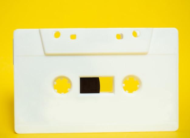 Cassette audio. bande audio blanche vintage avec fond jaune.
