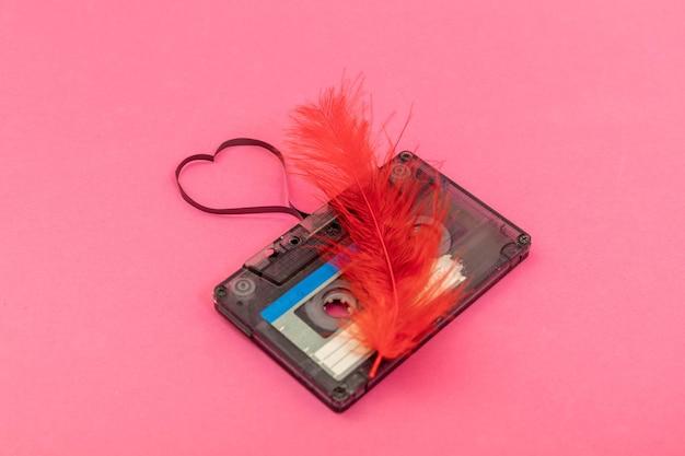 Cassette audio sur fond rose. film façonnant le coeur, carte postale de la saint-valentin. espace libre.