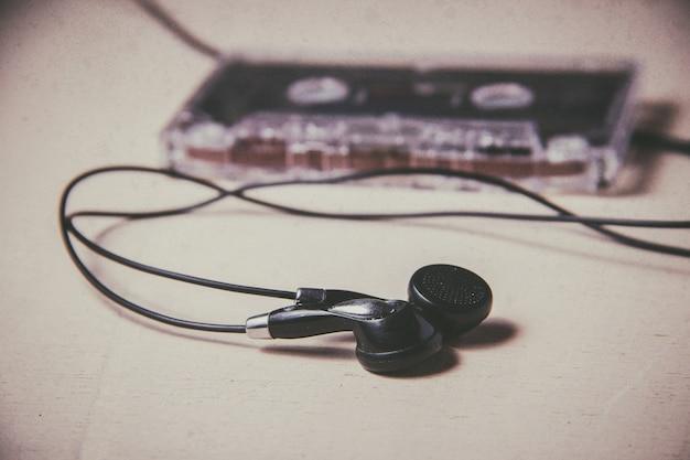 Cassette audio magnétique vintage et écouteurs sur le plancher en bois