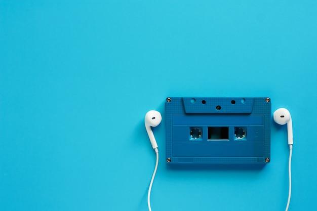Cassette audio rétro avec des écouteurs sur fond bleu pour le concept de musique et de relaxation