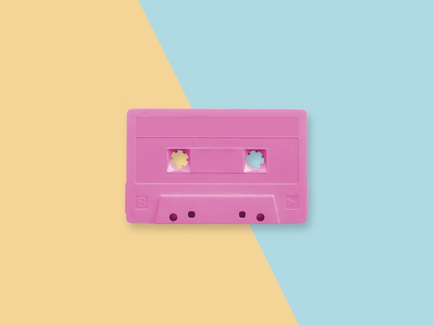 Cassette audio rose rétro sur une surface bicolore pastel