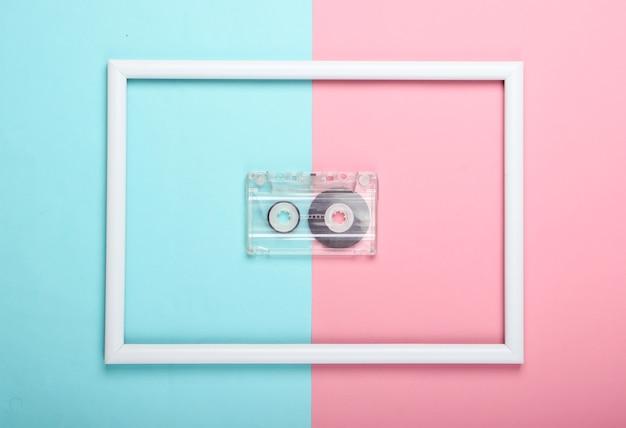 Cassette audio sur surface pastel bleu rose avec cadre blanc