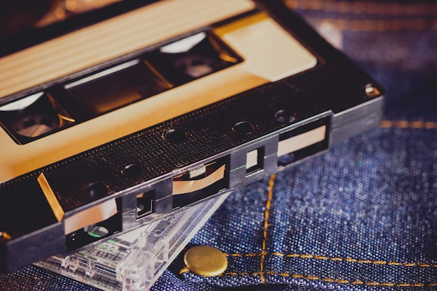 Cassette audio sur un tissu de jeans dans l'obscurité. lecteur de musique vintage des années 90.